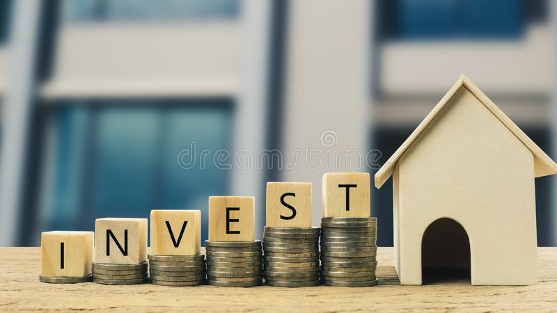 Real estate investment, Money savings for buy new home, Financial wealth management concept. Wooden block on stacked coins with wooden house model. Depicts the stock photography