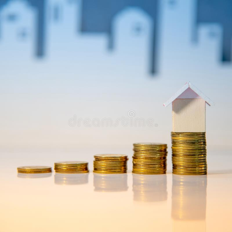 Real estate investment. Property ladder concept. Real estate investment or Home mortgage loan rate. Property ladder concept. Coins stack and house model on the royalty free stock photo