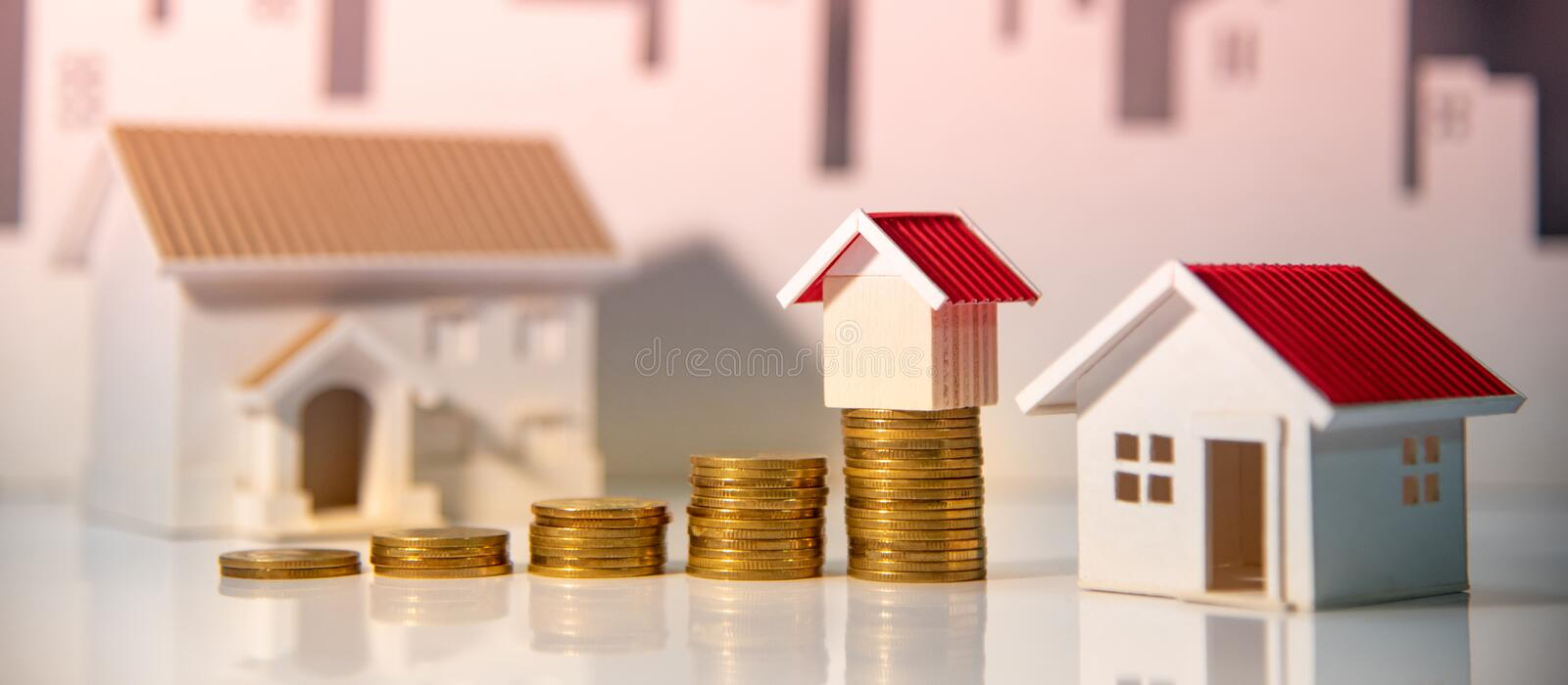 Real estate investment. Property ladder concept. Real estate investment or Home mortgage loan rate. Property ladder concept. Coins stack and house models on the royalty free stock photos