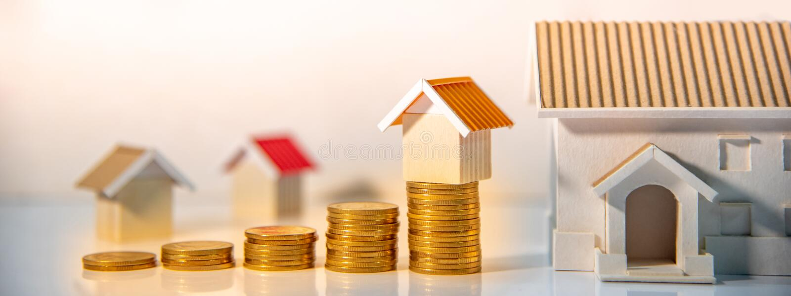 Real estate investment. Property ladder concept. Real estate investment or Home mortgage loan rate. Property ladder concept. Coins stack and house models on the royalty free stock image