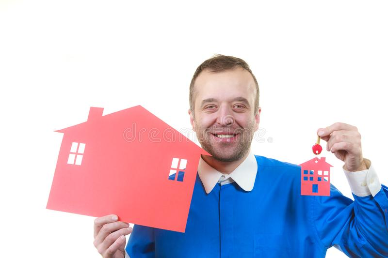 Real estate man with house model and keys. Man being real estate agent holding red house model and keys. Home ownership concept royalty free stock photography