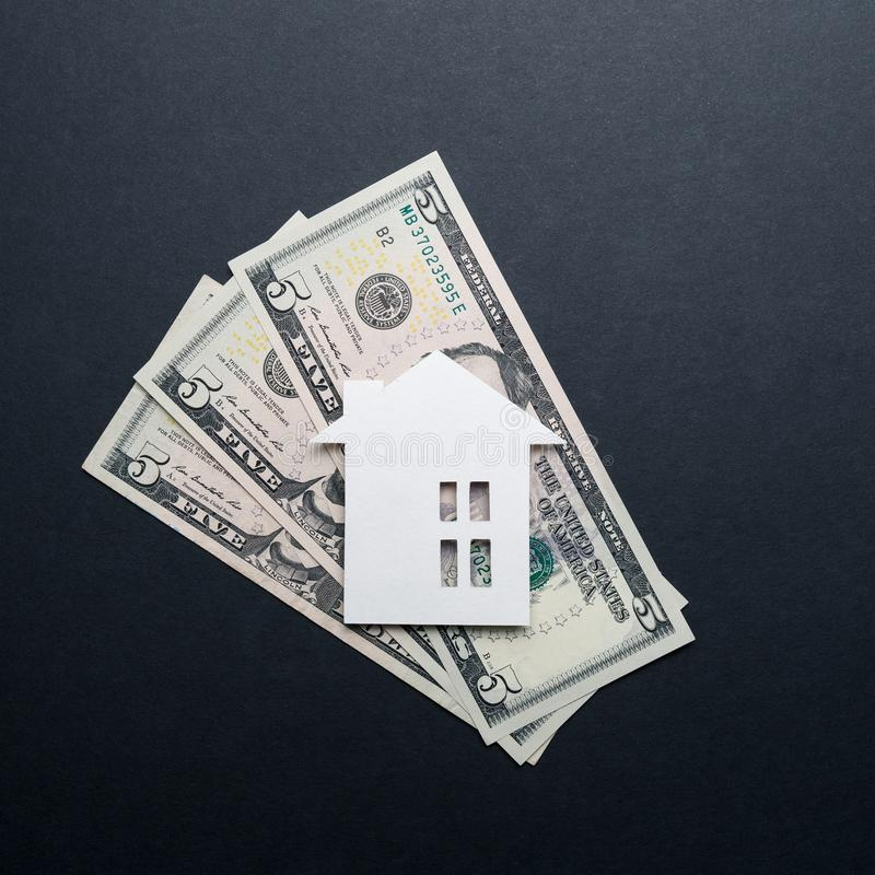 Real estate market concept. Minimalistic paper house on a black background. Top view. Flat lay. Copy space royalty free stock photo