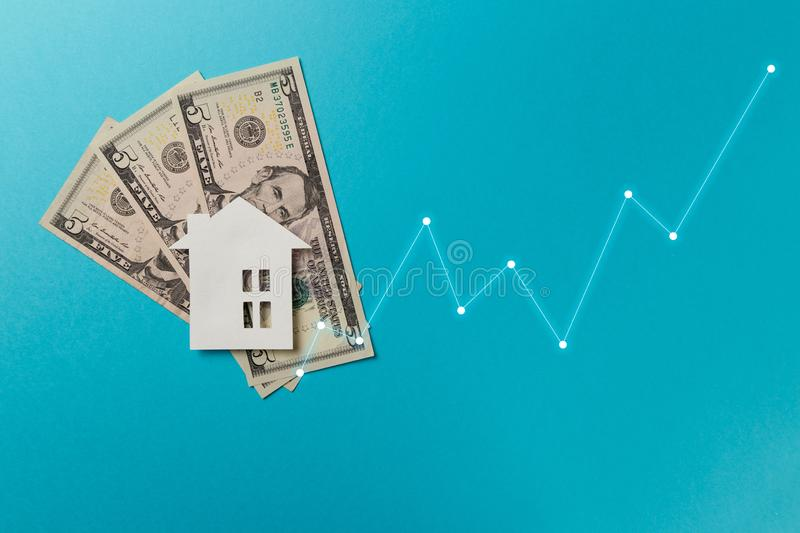 Real estate market concept. Minimalistic paper house on a blue background. Top view. Flat lay. Copy space royalty free stock images