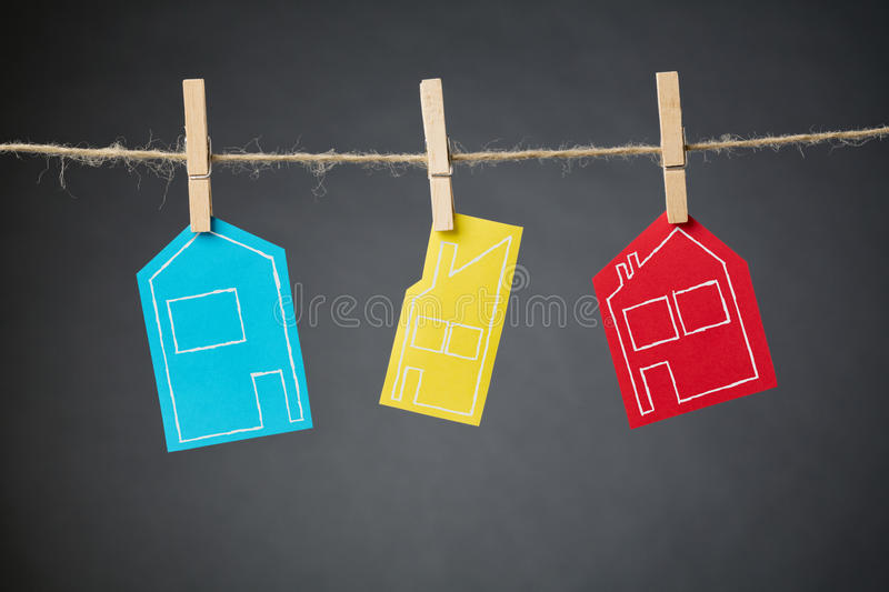 Real Estate Market - Hanging Houses. Hand drawn outlines of different types of houses on colorful pieces of paper hanging with clothespins from a rope line royalty free stock photo