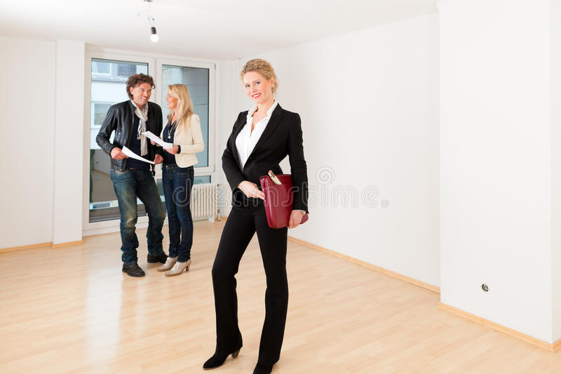Young couple looking for real estate with female realtor. Real estate market - young couple looking for real estate to rent or buy an apartment stock image