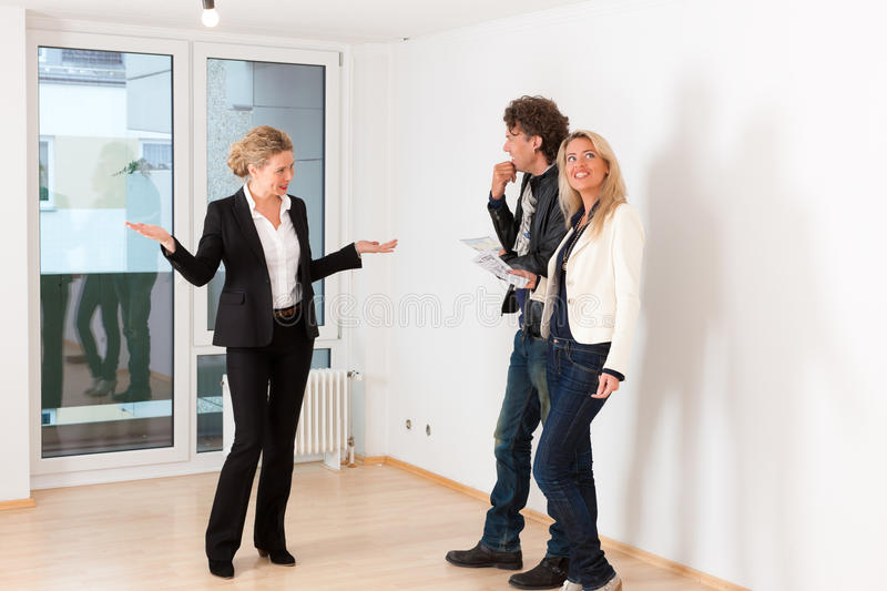 Young couple looking for real estate with female realtor. Real estate market - young couple looking for real estate to rent or buy an apartment stock photo