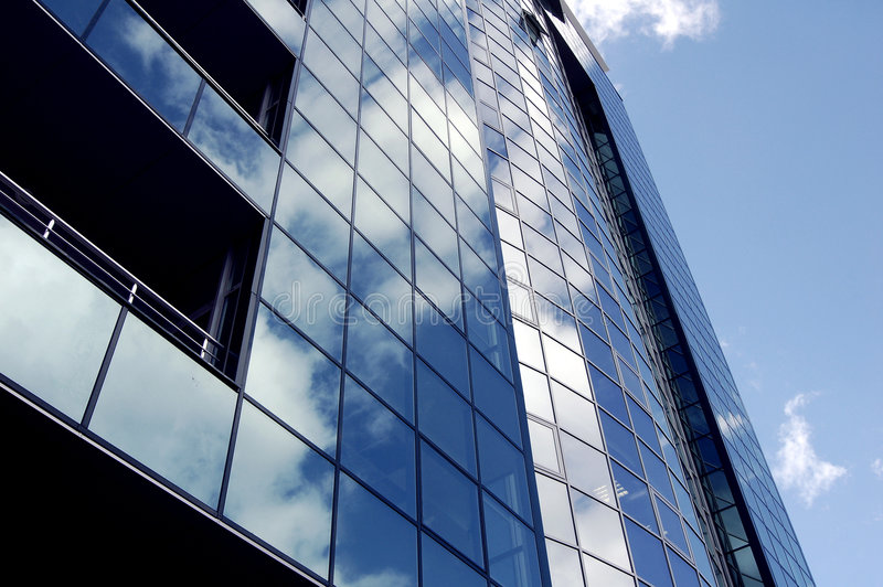 Real estate modern building facade. This photograph represents a real estate building facade with cloud reflections royalty free stock images