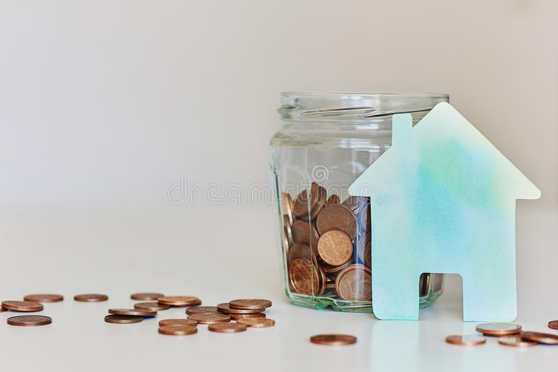 Real estate mortgage concept. Glass jar full of coins and green paper house royalty free stock photo