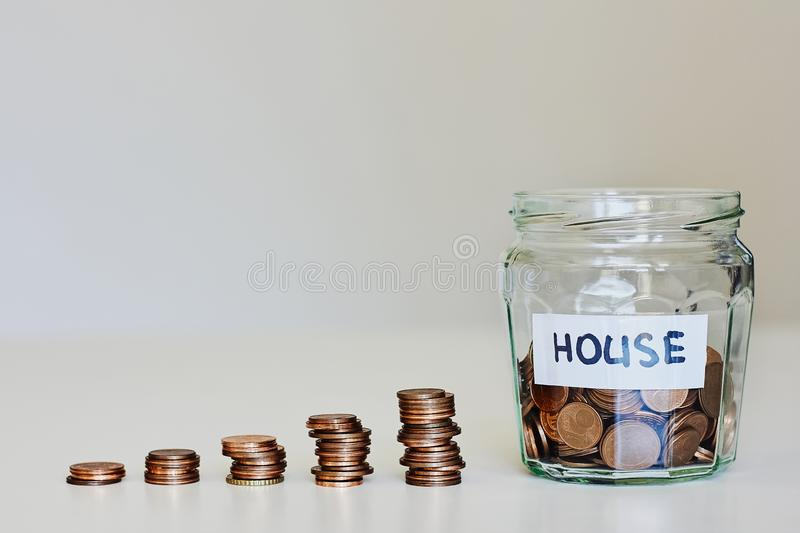 Real estate mortgage concept. Glass jar full of coins and sign house royalty free stock photo