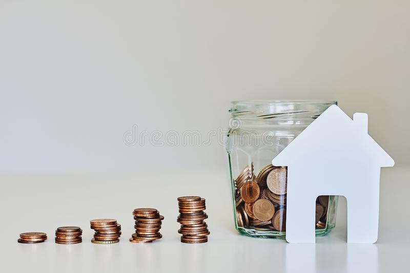 Real estate mortgage concept. Glass jar full of coins, stacks of coins and white paper house stock photos