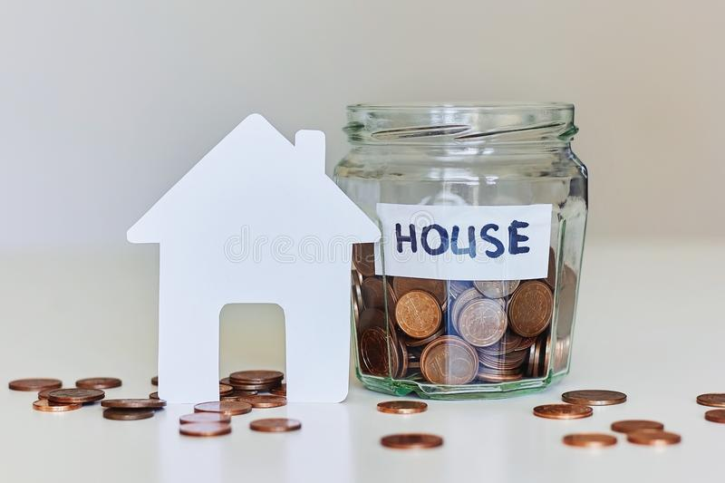 Real estate mortgage concept. Glass jar full of coins and white paper house stock photos