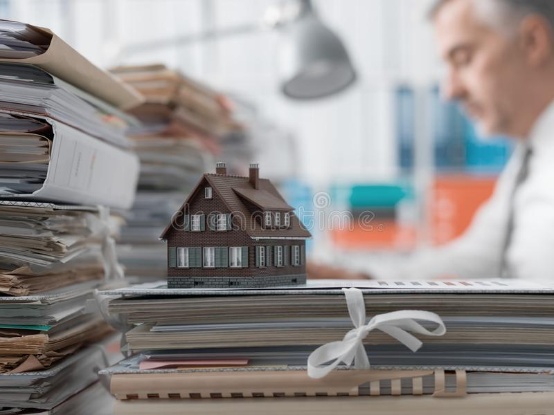 Real estate, mortgage loans and paperwork. Real estate agent working in the office and piles of paperwork, model house on the foreground and mortgage loan stock image