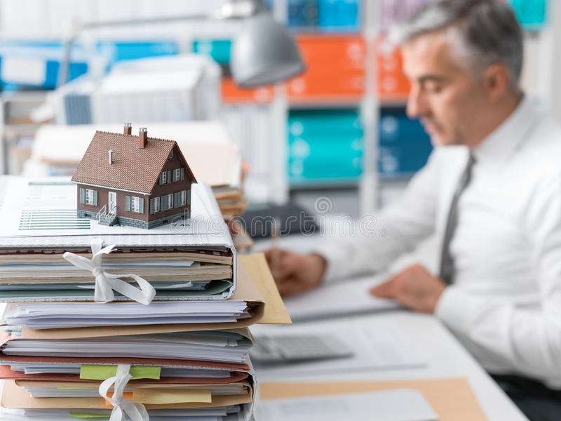 Real estate, mortgage loans and paperwork. Real estate agent working in the office and piles of paperwork, model house on the foreground and mortgage loan stock images