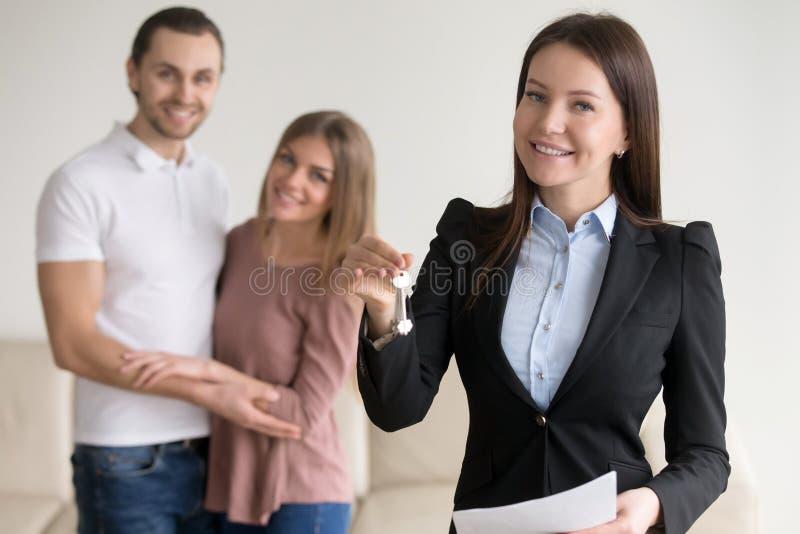 Real Estate negocia Corretor de imóveis de sorriso fêmea que mostra chaves ao plano fotos de stock