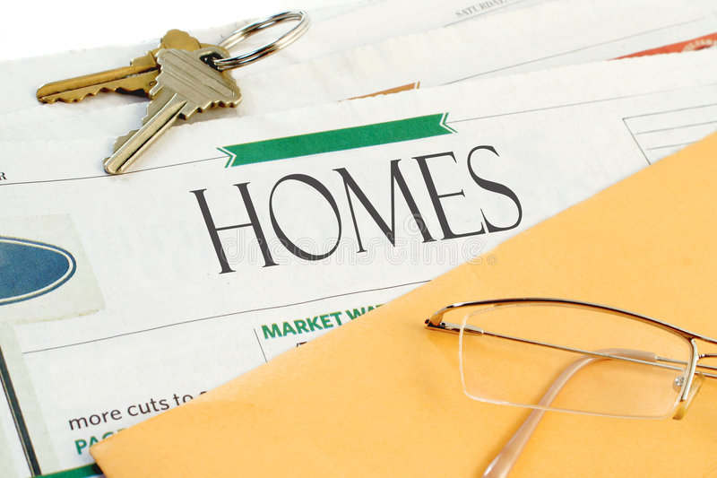 Real estate news. Real estate section of the newspaper with yellow envelope, eyeglasses and keys royalty free stock photos