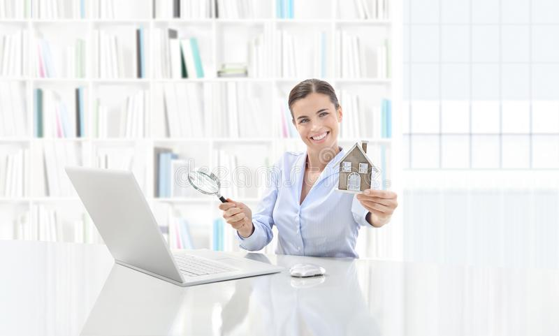 Real estate office, smiling woman agent working on computer with. Magnifying glass, search home concept royalty free stock photography