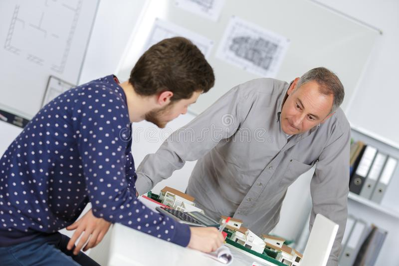 Real estate professor with student and scale model royalty free stock photography