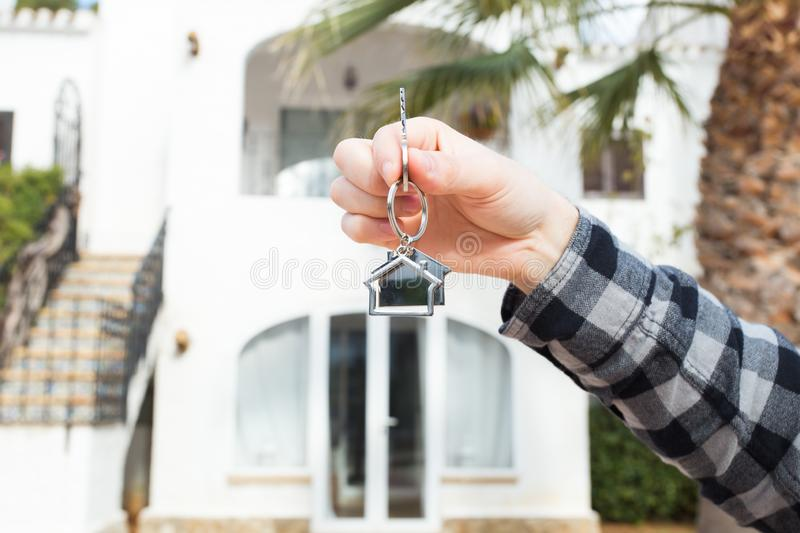 Real estate and property concept - Hand is holding house keys on house shaped keychain in front of a new home stock photography