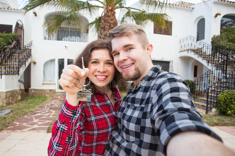 Real estate and property concept - Happy couple holding keys to new home and house miniature royalty free stock image