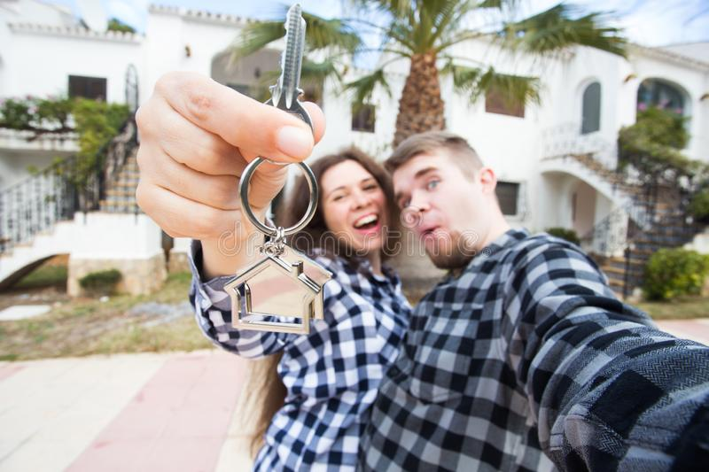 Real estate and property concept - Happy couple holding keys to new home and house miniature royalty free stock photo