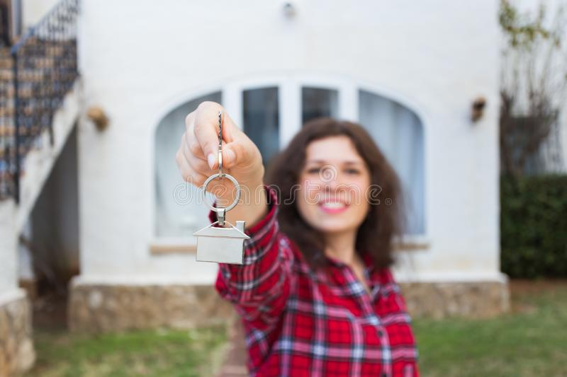 Real estate and property concept - Happy young woman in front of new home with new house keys royalty free stock photos