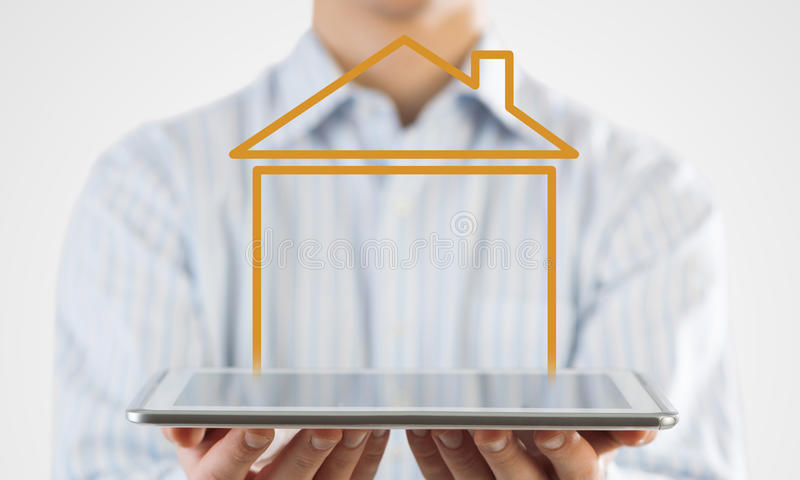 Real estate and property sales. Hand holding modern tablet and house sign on screen stock photo