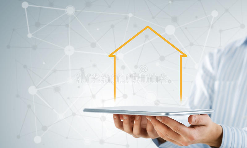 Real estate and property sales. Hand holding modern tablet and house sign on screen royalty free stock image