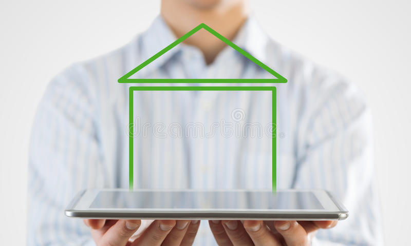 Real estate and property sales. Hand holding modern tablet and house sign on screen stock photos