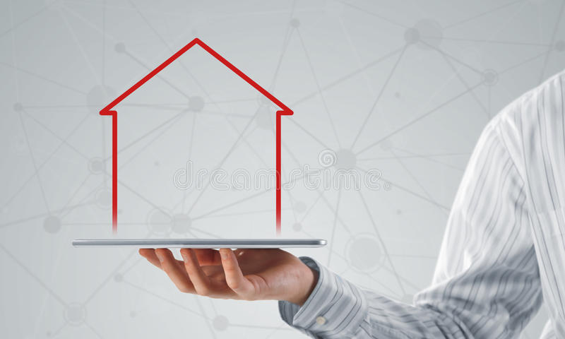 Real estate and property sales. Hand holding modern tablet and house sign on screen stock image