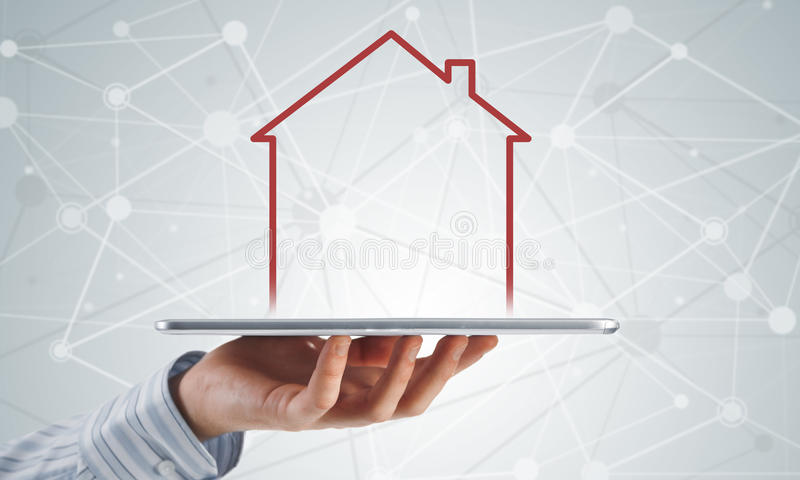 Real estate and property sales. Hand holding modern tablet and house sign on screen stock photography