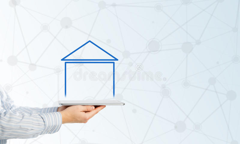 Real estate and property sales. Hand holding modern tablet and house sign on screen royalty free stock photography