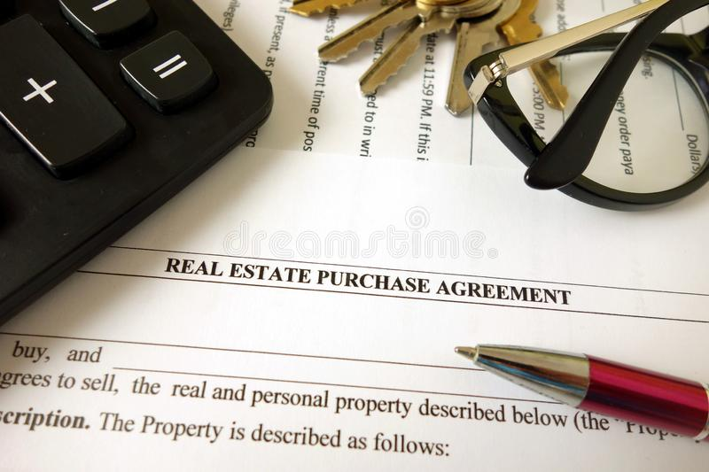 Real estate purchase agreement for filling with pen calculator keys and glasses. Closeup royalty free stock images
