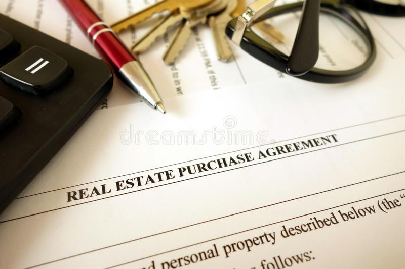 Real estate purchase agreement for filling with pen calculator keys and glasses. Closeup stock photos