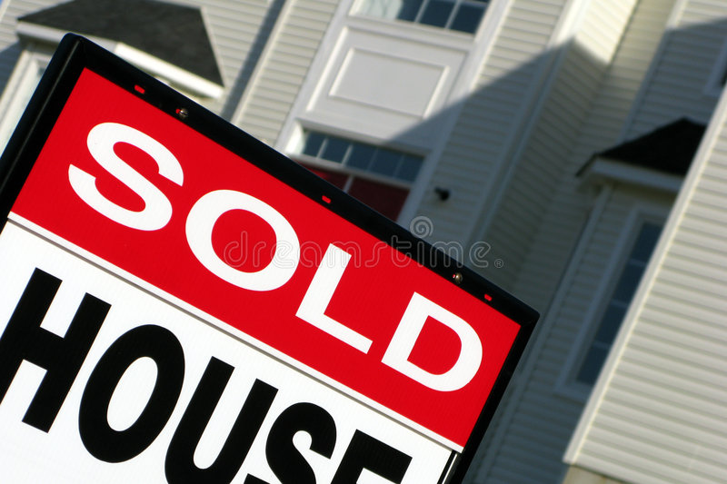 Real Estate Realtor Sold Sign and House For Sale. Real estate sold rider insert on a realtor advertising sign in front of a house for sale royalty free stock image