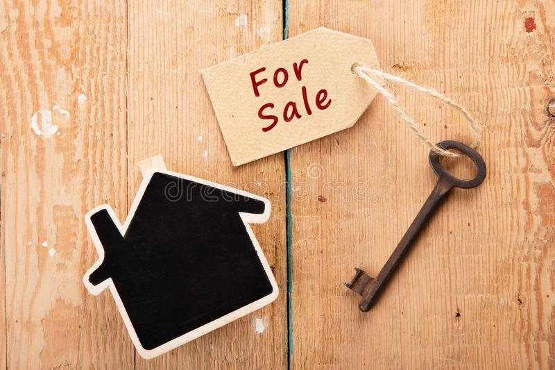 Real estate sale concept. Old key with tag home house renting keychain property wooden unlock door security business table access success landlord agent buy royalty free stock image
