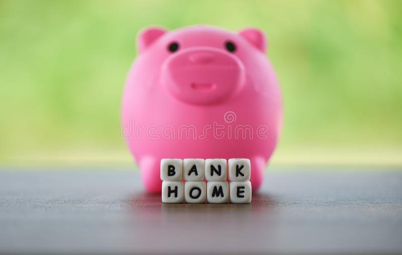 Real estate sale home savings loans market concept Pink piggy bank and dices words of bank home royalty free stock photography