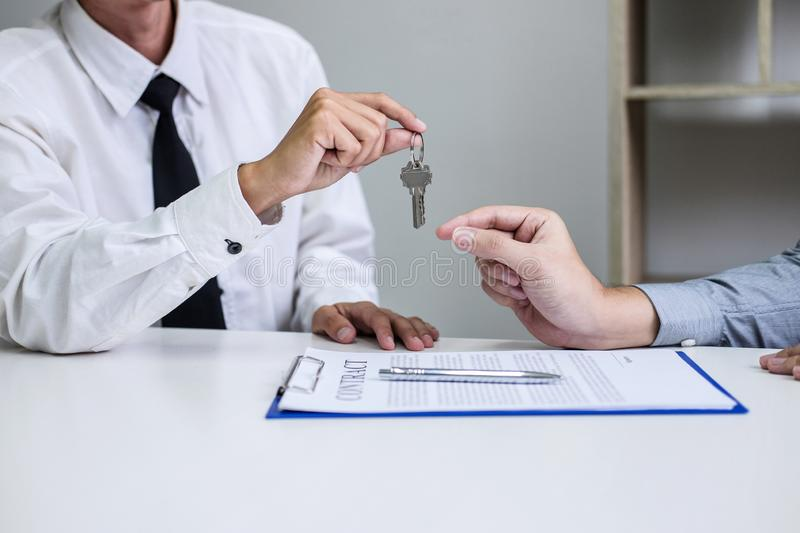 Real estate Sales manager giving keys to customer after signing rental lease contract of sale purchase agreement, concerning. Mortgage loan offer for and house royalty free stock image
