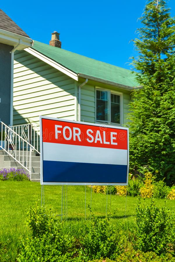 Real estate sign `For Sale` on front yard of a house.  royalty free stock photography