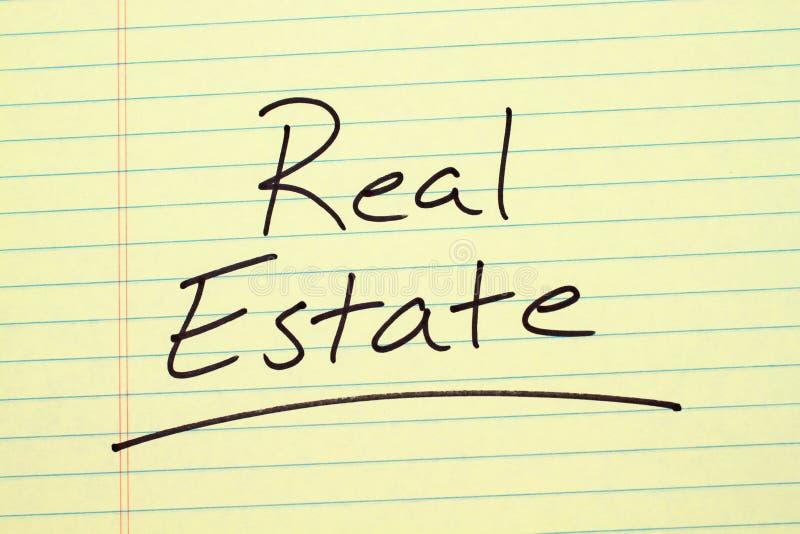 Real Estate su un blocco note giallo fotografia stock