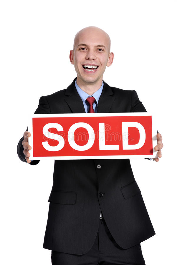 Real estate man holding a sold sign royalty free stock photography