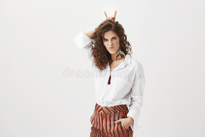 Real evil woman showing girl power. Portrait of cute and funny european female in stylish clothes, making serious and stock photo