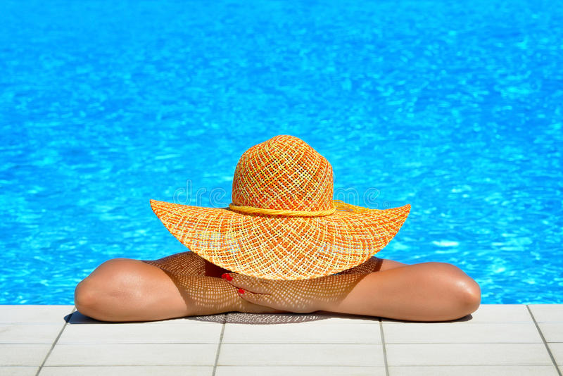 Real female beauty relaxing at swimming pool. Summer vacation concept royalty free stock image