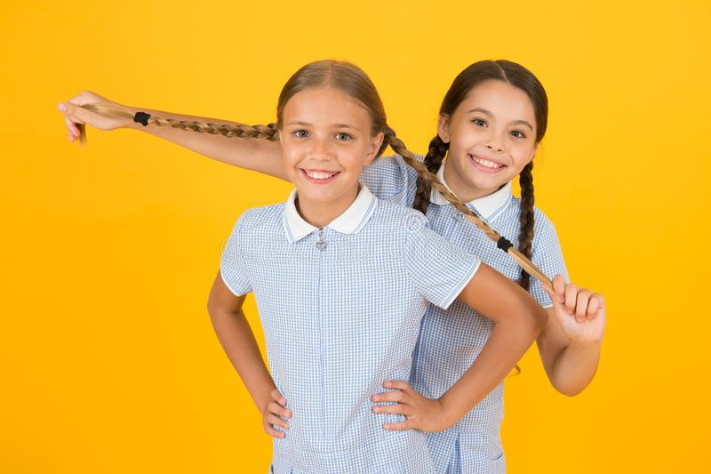 Real fun. happy friends on yellow background. fashion beauty. childhood happiness. sisterhood concept. small girls in. Vintage school uniform. children in retro stock photo