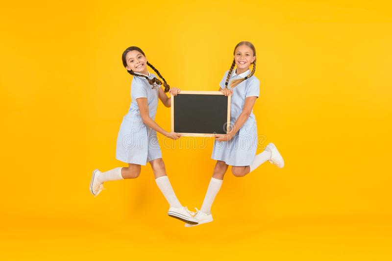 Real happiness. small girls jump with blackboard. children education. small girls presenting info. old school. copy. Space on board. happy friends in retro stock images