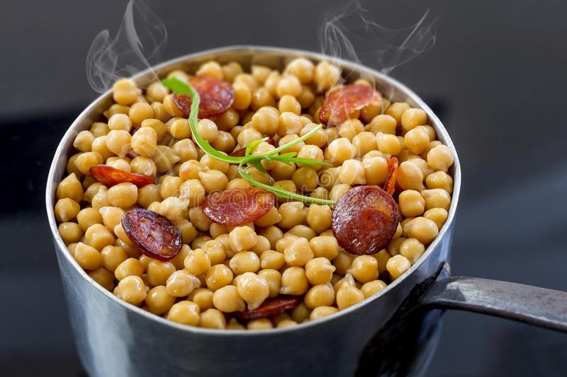 Real homemade chickpeas, steaming stew with chorizo on a black background stock photography