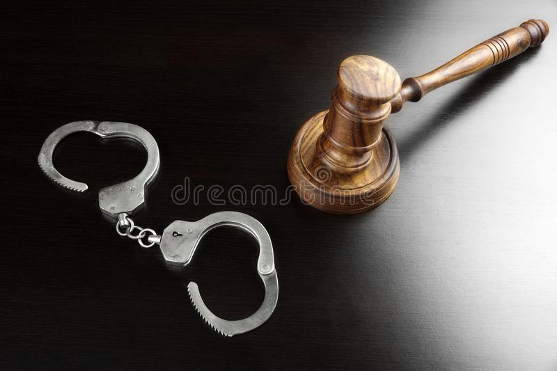 Real Judges Gavel And Handcuffs On The Black Table stock photos