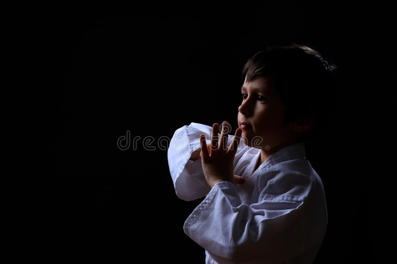 Real karate boy in white kimono isolated on dark background. Child ready for martial arts fight. Kid fighting at judo training. royalty free stock images