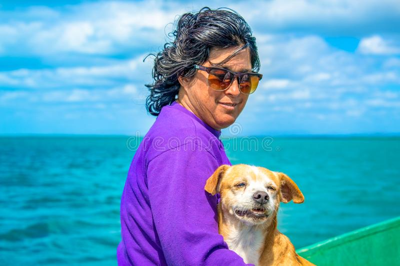 Real life Cuban people: woman with dog fishing in boat stock photos