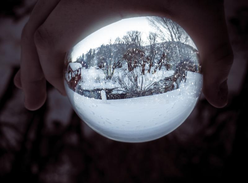 Real-Life Snow Globe. A boy holds a living snow globe in his hand against a dark, blurred background. The `snow globe` is a lensball reflecting a park in winter royalty free stock photos