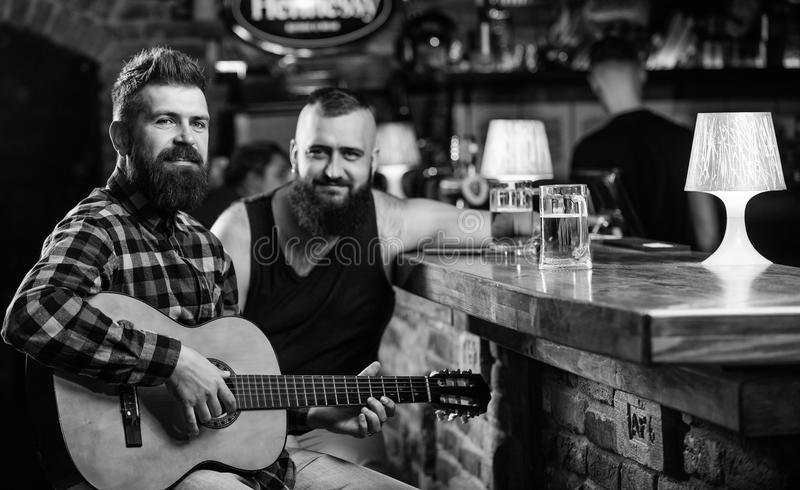 Real men leisure. Man play guitar in bar. Cheerful friends relax with guitar music. Friday relaxation in bar. Friends. Relaxing in bar or pub. Hipster brutal royalty free stock images